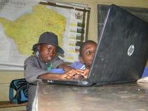 Bambini che utilizzano computer portatile nell'aula Fotografia Stock