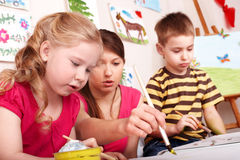 Bambini che verniciano con l'insegnante. Fotografia Stock