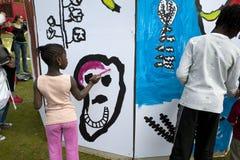 Bambini che verniciano parete murala Fotografia Stock