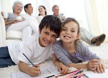 Bambini che verniciano sul pavimento con la famiglia in sofà Fotografia Stock