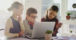 Bambini come uomini d'affari che per mezzo del computer portatile e della compressa digitale 4k archivi video