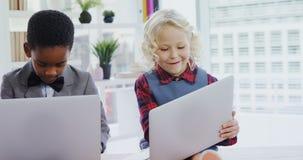 Bambini come uomini d'affari che per mezzo del computer portatile 4k archivi video