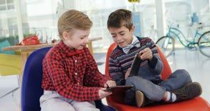 Bambini come uomini d'affari che per mezzo della compressa digitale 4k archivi video
