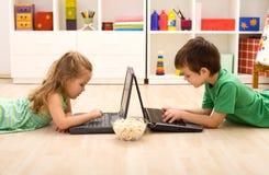 Bambini con i computer portatili e una ciotola di popcorn Fotografia Stock