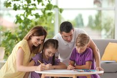 Bambini con i genitori che disegnano alla tavola all'interno fotografia stock