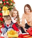 Bambini con il contenitore di regalo vicino all'albero di Natale. Immagine Stock Libera da Diritti