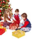 Bambini con il contenitore di regalo vicino all'albero di Natale. Fotografie Stock