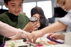 Bambini con il corredo di costruzione alla scuola di robotica Immagini Stock