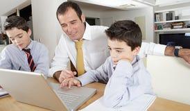 Bambini con il papà sul computer portatile Fotografia Stock