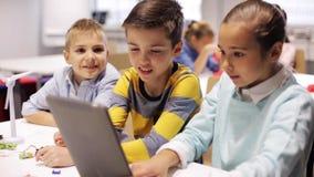 Bambini con il pc della compressa che programma alla scuola di robotica video d archivio