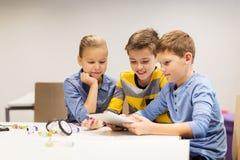 Bambini con il pc della compressa che programma alla scuola di robotica Fotografia Stock