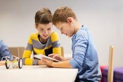 Bambini con il pc della compressa che programma alla scuola di robotica Immagine Stock