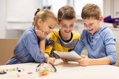 Bambini con il pc della compressa che programma alla scuola di robotica Fotografie Stock Libere da Diritti