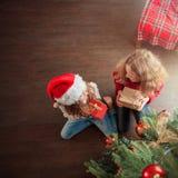 Bambini con il regalo sotto l'albero di Natale fotografie stock