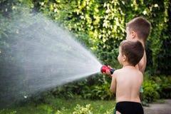 Bambini con il tubo flessibile Fotografie Stock Libere da Diritti