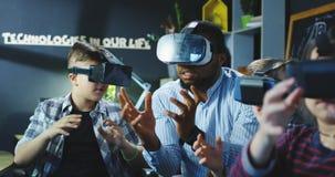 Bambini con l'insegnante che esplora mondo virtuale Immagine Stock