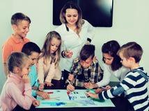 Bambini con l'insegnante che riunisce nell'aula immagine stock libera da diritti