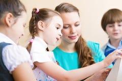 Bambini con l'insegnante impegnato nella pittura fotografia stock