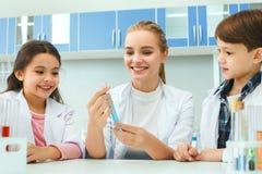Bambini con l'insegnante nella lezione del liquido del laboratorio della scuola Immagini Stock Libere da Diritti
