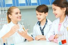 Bambini con l'insegnante nella spiegazione di lezione del laboratorio della scuola immagine stock