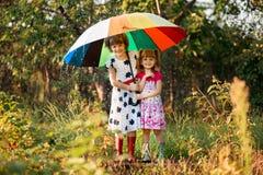 Bambini con l'ombrello variopinto che gioca in pioggia della doccia di autunno Le bambine giocano in parco da tempo piovoso fotografie stock