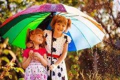 Bambini con l'ombrello variopinto che gioca in pioggia della doccia di autunno Le bambine giocano in parco da tempo piovoso fotografia stock