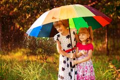 Bambini con l'ombrello variopinto che gioca in pioggia della doccia di autunno Le bambine giocano in parco da tempo piovoso immagini stock libere da diritti