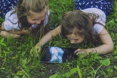 Bambini con la compressa che si trova nell'erba Fotografia Stock Libera da Diritti