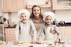Bambini con la madre in cucina La famiglia è pronta a srotolare la pasta immagine stock