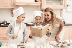 Bambini con la madre in cucina La famiglia sta leggendo la ricetta in libro di cucina fotografie stock