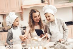 Bambini con la madre in cucina La famiglia sta leggendo la ricetta sulla compressa immagini stock