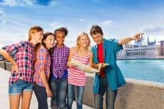 Bambini con la mappa che sta insieme sull'argine Fotografia Stock
