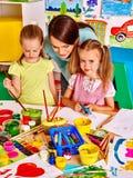 Bambini con la pittura dell'insegnante Immagine Stock