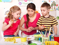 Bambini con la pittura dell'insegnante nella stanza del gioco. Fotografia Stock