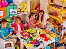 Bambini con la pittura della donna dell'insegnante sulla carta nell'asilo Fotografie Stock Libere da Diritti