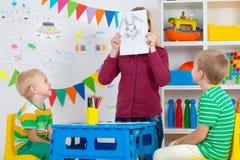 Bambini con le immagini di tiraggio e della mamma nella stanza dei bambini immagine stock
