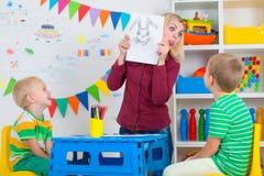 Bambini con le immagini di tiraggio e della mamma nella stanza dei bambini fotografie stock libere da diritti