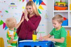 Bambini con le immagini di tiraggio e della mamma nella stanza dei bambini fotografia stock