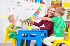 Bambini con le immagini di tiraggio e della mamma nella stanza dei bambini fotografia stock libera da diritti