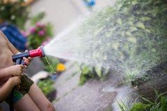 Bambini con le piante di innaffiatura del tubo flessibile Fotografie Stock