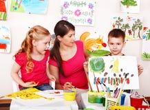 Bambini con le vernici di tiraggio dell'insegnante in aula. fotografie stock
