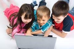 Bambini con un computer portatile Fotografia Stock