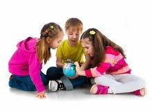 Bambini con un globo del mondo Immagini Stock Libere da Diritti