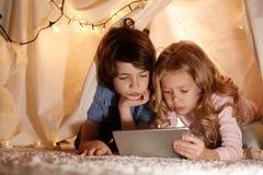 Bambini concentrati che praticano il surfing Internet sulla lavagna per appunti Fotografia Stock