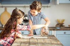 Bambini contenti che mangiano alcuni biscotti Immagini Stock