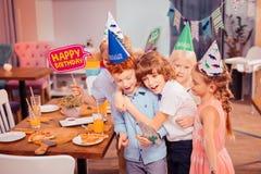 Bambini contentissimi positivi che prendono foto con il ragazzo di compleanno fotografie stock libere da diritti