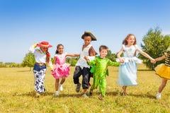 Bambini correnti che portano i costumi fuori nel campo Fotografia Stock