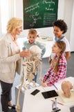 Bambini curiosi allegri che ascoltano l'insegnante Immagini Stock Libere da Diritti