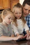 Bambini d'aiuto del papà con un telefono fotografia stock libera da diritti