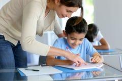 Bambini d'aiuto dell'insegnante con la lezione Immagine Stock